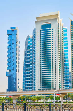 DUBAI, UAE - MARCH 2, 2020: The view of high rises of Jumeirah Lake Towers complex behind the metro viaduct and Sheikh Zayed Road, on March 2 in Dubai