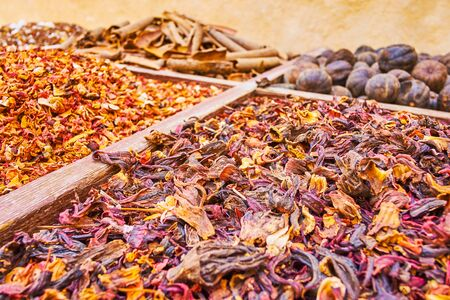 The close up of the heaps of hibiscus tea, rose petals, cinnamon and other herbs and spices in Dubai market, UAE