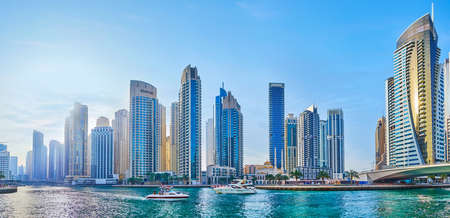 DUBAI, UAE - MARCH 2, 2020: Panorama of Dubai Marina with canal, bridge, forest of modern skyscrapers, Park Island towers and floating yachts, on March 2 in Dubai
