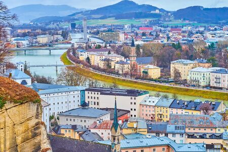 The cityscape of historical district of Salzburg with Austrian classic style houses and winding Salzach river dividing city on two parts