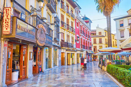 GRANADA, SPAIN - SEPTEMBER 25, 2019: Walk the scenic Calle Capuchinas street with historical townhouses, restaurants, cafes, bars, trimmed bushes and tall palm trees, on September 25 in Granada Editoriali