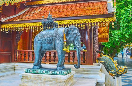 The bronze elephant statue at the side wall of Vihara (shrine), guarded by mom mythic creature, seen on background, Wat Phra That Doi Suthep temple, Chiang Mai, Thailand