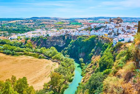 The steep rock, topped with medieval Arcos housing with curved Guadalete river at its foot, Spain Stock Photo