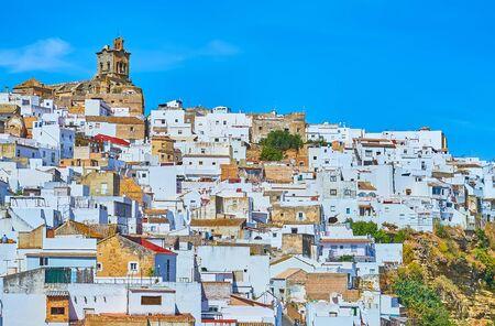 The medieval stone San Pedro church dominates the white dense houses of old Arcos, Spain