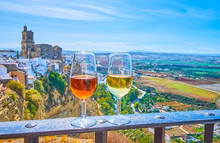 Enjoy the glass of Sherry wine with a view on medieval white town (pueblo blanco) of Arcos, located on the cliff top and famous for its unique medieval architecture, Spain