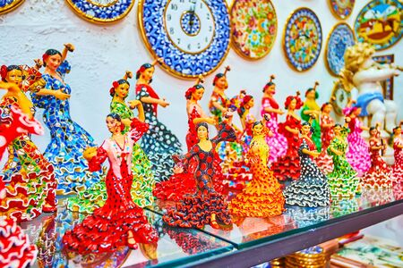 The tourist shop offers large amount of porcelain souvenirs, such as wall clocks or figurines of flamenco dancers in colorful dresses, Arcos, Spain
