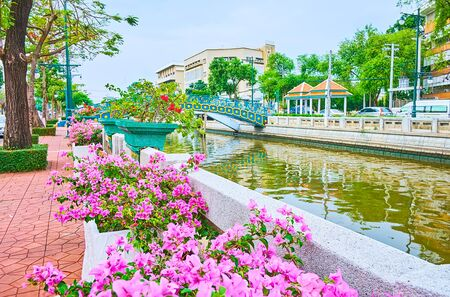 The view on the bridge across the Khlong Phadung Krung Kasem canal, that is lined with stone balusters, trees, blooming bougainvillea bushes, vintage streetlights, Dusit, Bangkok, Thailand
