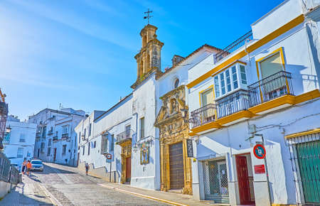 ARCOS, SPAIN - SEPTEMBER 23, 2019: The hilly Calle Corredera street with dense white houses and Hospital - San Juan de Dios church, sandwiched among the living buildings, on September 23 in Arcos Editoriali