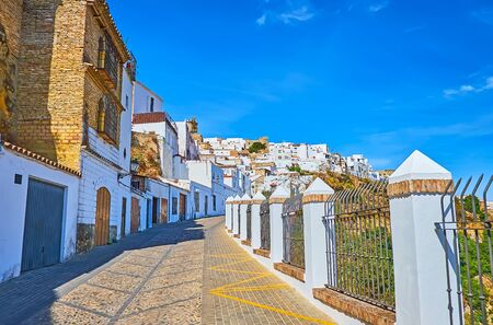 The narrow streets leads to the old city hill, occupied with medieval white houses and churches, Arcos, Spain