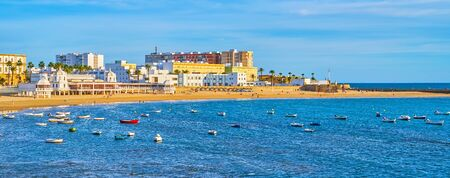Panorama of La Caleta beachline with coastal cafes, sunshades, recreation zone and small fishing boats, moored in harbor, Cadiz, Spain Фото со стока