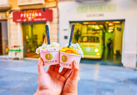 CADIZ, SPAIN - SEPTEMBER 23, 2019: Two cardboard cups with ice-cream in front of cafe in Calle Ancha, on September 23 in Cadiz Editoriali