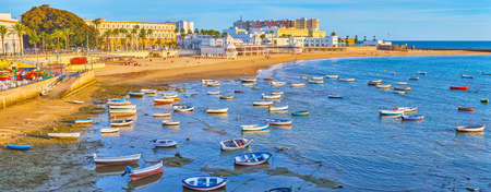 CADIZ, SPAIN - SEPTEMBER 23, 2019: Panorama of small fishing boats on shallow of La Caleta harbor with sand beach and coastal neighborhood on background, on September 23 in Cadiz Editorial
