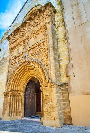 The medieval stone Spanish Plateresque style gate of Nuestra Senora de la O (Our Lady of O) parish church with fine carvings, patterns and wall sculptures, Sanlucar, Spain