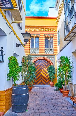The shady yard with plants in pots, old cask and gate of historic Mudejar mansion with zigzag pattern, Sanlucar, Spain
