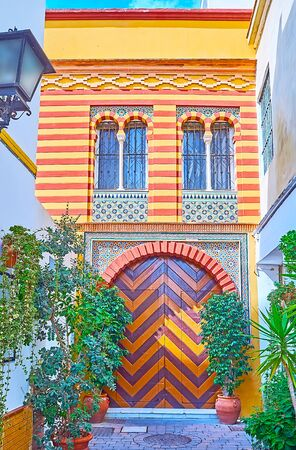 The gate of historic Mudejar mansion with zigzag pattern, tile door frame and colorful wall, decorated with fine Islamic ornaments, Sanlucar, Spain