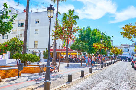 SANLUCAR, SPAIN - SEPTEMBER 22, 2019: The outdoor cafes and lush trees in Plaza de la Paz square in old town, on September 22 in Sanlucar