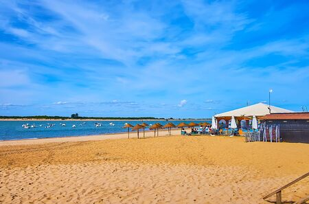 Las Piletas beach on Guadalquivir river with summer terrace of beach cafe and boats, bobbing on the waves, Sanlucar, Spain
