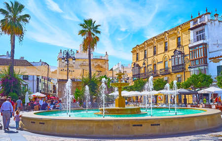 SANLUCAR, SPAIN - SEPTEMBER 22, 2019: The crowded Plaza del Cabildo square, decorated with scenic fountain, is lined with popular tourist restaurants and old townhouses, on September 22 in Sanlucar Imagens - 150301922