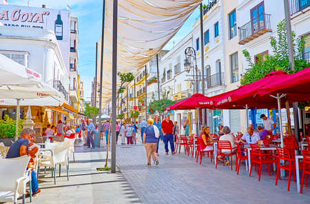 SANLUCAR, SPAIN - SEPTEMBER 22, 2019: The vibrant life in Calle Ancha street, full of fashion stores, cafes, restaurants and souvenir shops, attracting tourists, on September 22 in Sanlucar Imagens - 150301928
