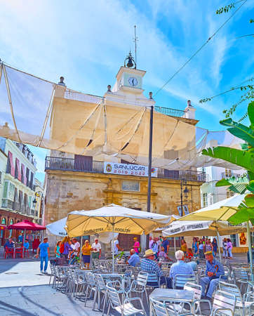 SANLUCAR, SPAIN - SEPTEMBER 22, 2019: The small outdoor cafe in Plaza del Cabildo square next to historic building of Municipal Library, on September 22 in Sanlucar Editorial