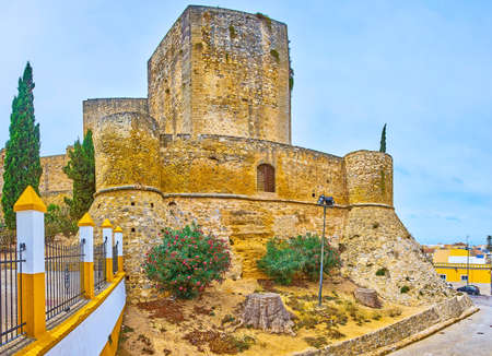 The medieval stone rampart of Santiago Castle with watchtowers and Torre del Homenaje tower, rising over the walls, Sanlucar, Spain