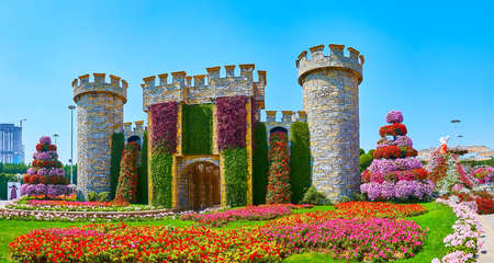DUBAI, UAE - MARCH 5, 2020: The facade of the fort, decorated with green plants on wall and waterfalls of red petunias, Miracle Garden, on March 5 in Dubai Imagens - 151082083