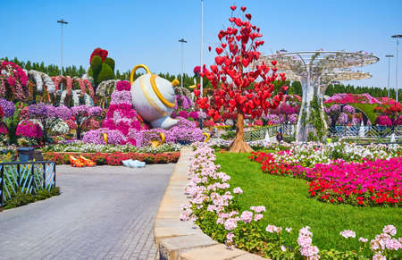 DUBAI, UAE - MARCH 5, 2020: Walk the Miracle Garden alley and enjoy its scenic decorations - love tree with hanging hearts, giant sunshades and teapot installation amid petunia flower bed, on March 5 in Dubai Imagens - 151082084