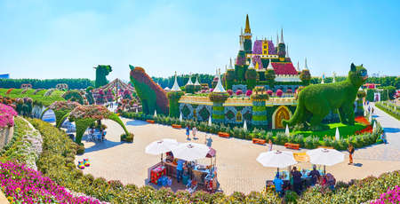 DUBAI, UAE - MARCH 5, 2020: Panorama of fairytale castle of Miracle Garden, surrounded by giant cats installations, flower beds, walking alleys and food stalls, on March 5 in Dubai Редакционное