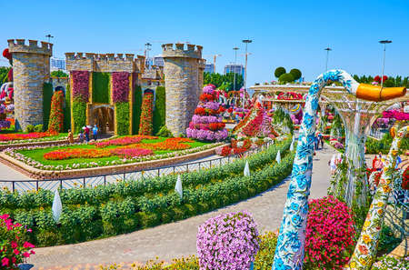 DUBAI, UAE - MARCH 5, 2020: The small stone fort, surrounded by flower beds, and decorated by green plants and waterfalls of petunias, located in Miracle Garden, on March 5 in Dubai 新聞圖片