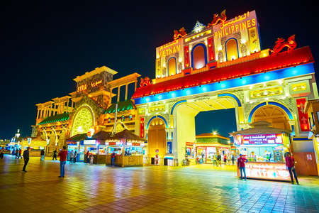 DUBAI, UAE - MARCH 5, 2020: The facades of Syria, Vietnam and Philippines Pavilions of Global Village Dubai with bright lights and molding, on March 5 in Dubai Imagens - 151082099