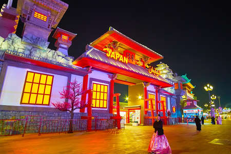 DUBAI, UAE - MARCH 5, 2020: The scenic facade of Japan Pavilion of Global Village Dubai with gable roof, wooden columns and supports, stone-like walls and blooming Japanese cherry (sakura) tree replica, on March 5 in Dubai