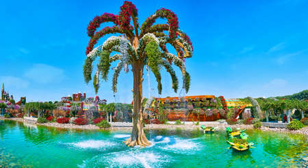 DUBAI, UAE - MARCH 5, 2020: Panoramic view of the pond of Miracle Garden with a palm tree-shaped fountain and sculptures of turtles, serving as the flower pots, on March 5 in Dubai Imagens - 151082111