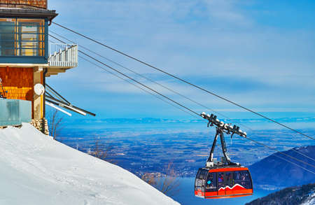 EBENSEE, AUSTRIA - FEBRUARY 24, 2019: The modern bright red tram of air lift, riding along the snowy slope of Feuerkogel mount, on february 24 in Ebensee