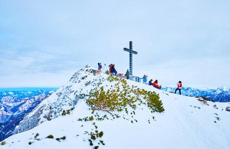 EBENSEE, AUSTRIA - FEBRUARY 24, 2019: The sportsmen enjoy the views from the peak of Alberfeldkogel mount, topped with Europakreuz (Europe Cross), on february 24 in Ebensee Imagens - 151377305