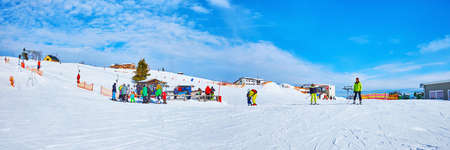 EBENSEE, AUSTRIA - FEBRUARY 24, 2019: Panorama of Feuerkogel mountain plateau with a view on kids ski zone, button ski lift and training ski track, on february 24 in Ebensee. Imagens - 151377309