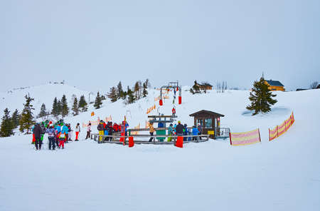 EBENSEE, AUSTRIA - FEBRUARY 24, 2019: The queue to the button ski lift on training ski zone for children, located on gentle slope of Feuerkogel mount, on february 24 in Ebensee Imagens - 151377314