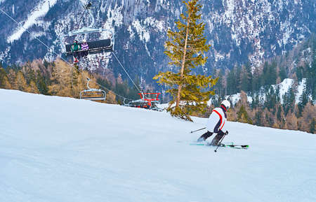 The skier makes the downhill from the steep slope of Feuerkogel mount, with a view on riding chairlift, Ebensee, Salzkammergut, Austria