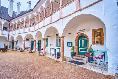 GMUNDEN, AUSTRIA - FEBRUARY 22, 2019: The famous Orther Stub'n restaurant located in historical medieval Schloss Ort castle with the entrance under arcade of courtyard, on February 22 in Gmunden Imagens - 151377319