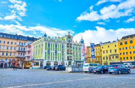 GMUNDEN, AUSTRIA - FEBRUARY 22, 2019: Rathausplatz (Town Hall Square) is the central sqaure with large car parking zone and magnificent green town hall building on the edge, on February 22 in Gmunden