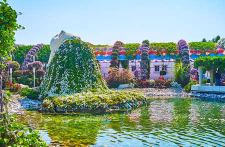 DUBAI, UAE - MARCH 5, 2020: The installation of the woman's head with floral hair, hanging to the pond in Miracle Garden, on March 5 in Dubai