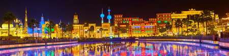 DUBAI, UAE - MARCH 5, 2020: Panorama with amazing skyline of Global Village Dubai pavilions and lighted pond on the foreground, on March 5 in Dubai