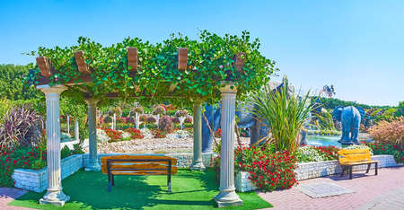 DUBAI, UAE - MARCH 5, 2020: Panorama of Miracle Garden with shady pavilion, located at the pond with elephant sculptures, on March 5 in Dubai