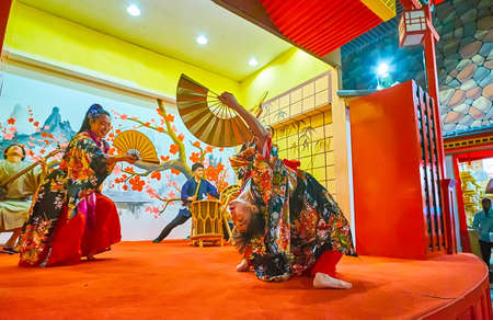 DUBAI, UAE - MARCH 5, 2020: The artists, dressed kimono, perform the Japanese dance with fans on stage of Japan Pavilion in Global Village Dubai, on March 5 in Dubai Publikacyjne