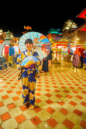 DUBAI, UAE - MARCH 5, 2020: The portrait of young Japanese girl, dressed in kimono, holding traditional fan and oil-paper umbrella, Japan Pavilion of Global Village Dubai, on March 5 in Dubai