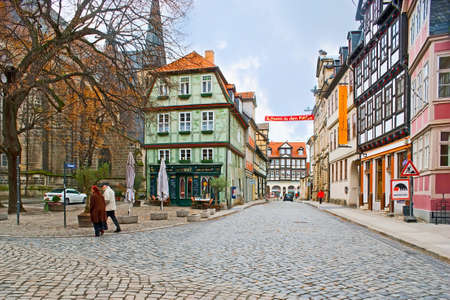 QUEDLINBURG, GERMANY - NOVEMBER 22, 2012: The cityscape with colored half-timbered houses, restaurants and a view on Kornmarkt street, on November 22 in Quedlinburg