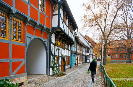 The line of colorful half-timbered houses, located in Neustadter Kirchhof, adjacent to the garden of St Nicholas church, Quedlinburg, Harz, Germany