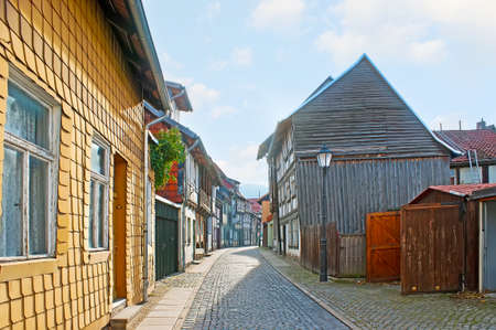 The old Kochstrasse street of Wernigerode old town with preserved half-timbered houses and houses, covered with wooden tiles, Wernigerode, Germany Banco de Imagens