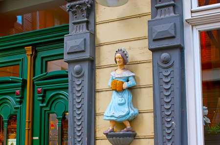 WERNIGERODE, GERMANY - NOVEMBER 23, 2012: The vintage wooden sculpture of beer waitress on the wall of restaurant, located in Breite Strasse, on November 23 in Wernigerode