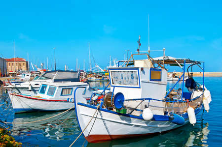 The small fishing boats are moored along the shore of Venetian port of Chania, Crete, Greece