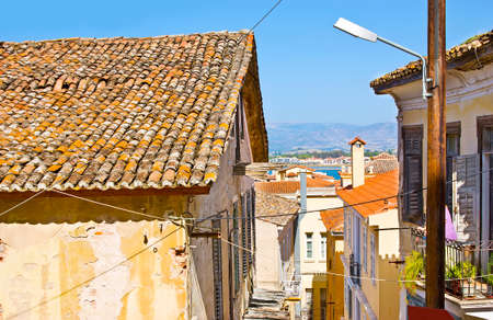 The hilly streets of old town overlooks the old tile roofs of living buildings and the coast of Argolic Gulf in background, Nafplio, Greece Banco de Imagens